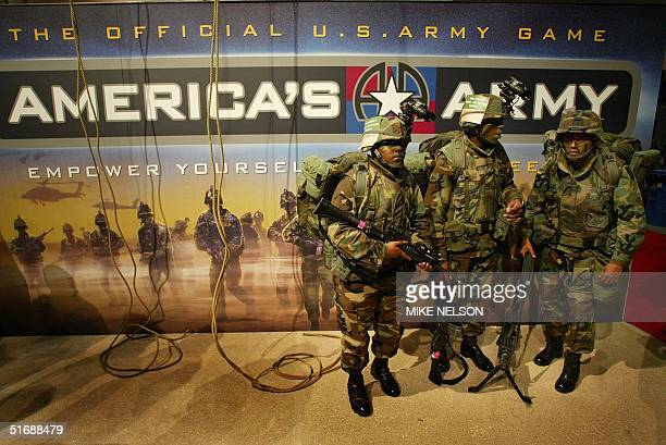 "Army soldiers stand next to an advertisement for the Army's computer game ""America's Army"", which was unveiled 22 May 2002 at the Electronic..."