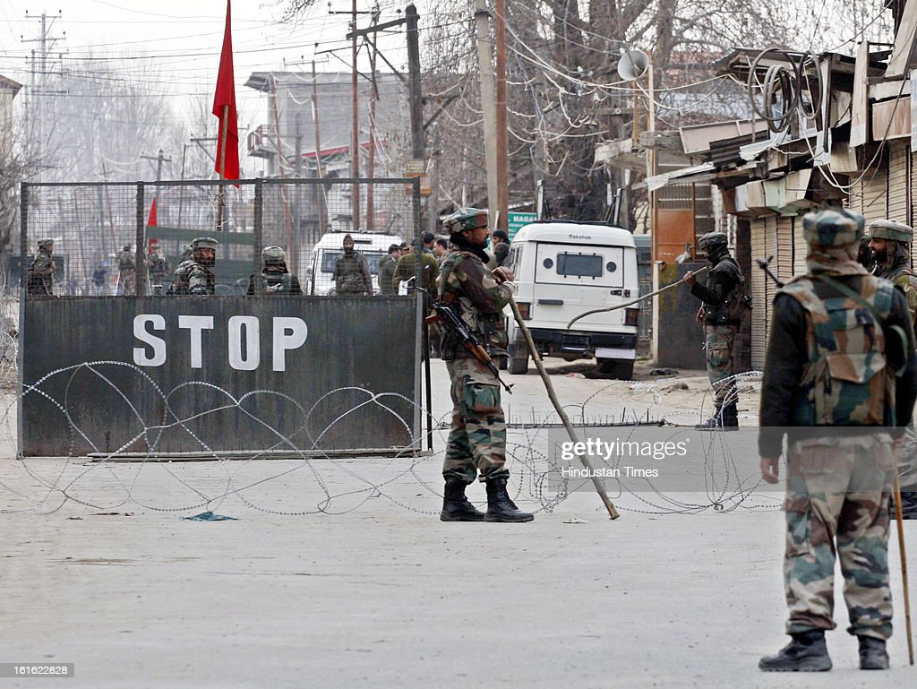 Army soldiers stands near a barricade on February 13, 2013 in Sopore some 50 Km from Srinagar, India. Curfew was was imposed by the authorities last Saturday to control Law and order situation after the execution of Parliament attack convict Afzal Guru.