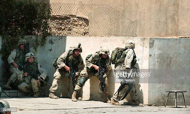 S Army soldiers take cover during a gun battle following a rocket propelled grenade attack on US troops August 7 2003 in dowtown Baghdad Iraq At...