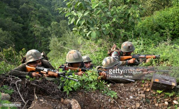 Army soldiers take position during an encounter with armed suspected militants at Kakriyal village Reasi district on September 13 2018 in Jammu India...