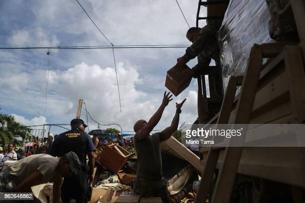 Army soldiers unload food, provided by FEMA, to be passed on to residents in a neighborhood without grid electricity or running water on October 17,...