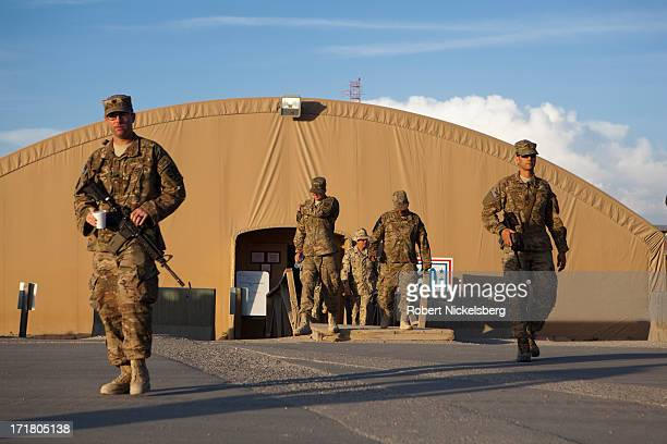Army soldiers walk in front of a hangar May 11, 2013 at Bagram Air Base, Afghanistan. U.S. Soldiers and marines are part of the NATO troop withdrawal...