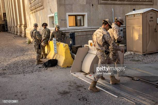 Army soldiers watch as fellow Coalition soldiers pass by near the entrance to the International Zone on May 30, 2021 in Baghdad, Iraq. Coalition...