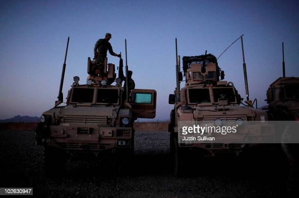 S Army soldiers with a route clearance unit from 3rd Platoon 123rd Engineer Company 105th Engineer Battalion take a gun down from the top of an MRAP...