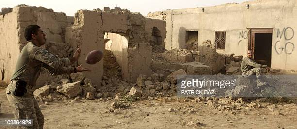 Army soldiers with the 101st Airborne Division Alpha Battery 1-320th play American Football in the ruins of a compound at a patrol base named...