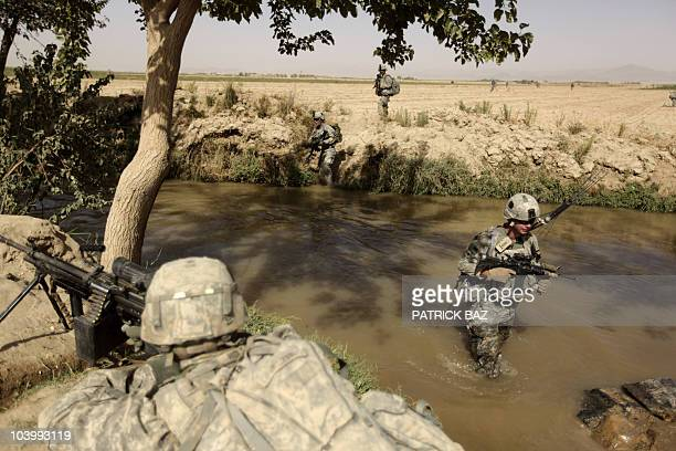 Army soldiers with the 101st Airborne Division Alpha Battery 1-320th, cross a river in the village of Saidon Kalacheh on the outskirts of the village...