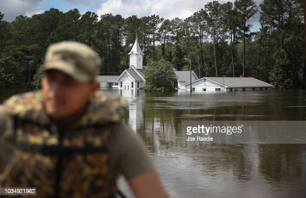 Army Spc. Daniel Ochoa from the Eighth Ordnance Company, Fort Bragg, rides past the flooded Church of the Covenant in a rescue truck as the Little...