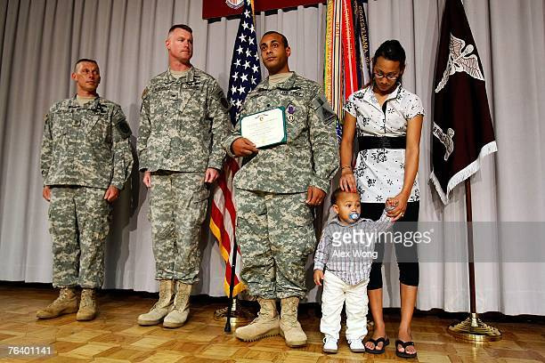 Army Spc George Wilson of San Diego poses with his wife Margaret son Jayden and Col Terrence McKendrick during a Purple Heart presentation ceremony...