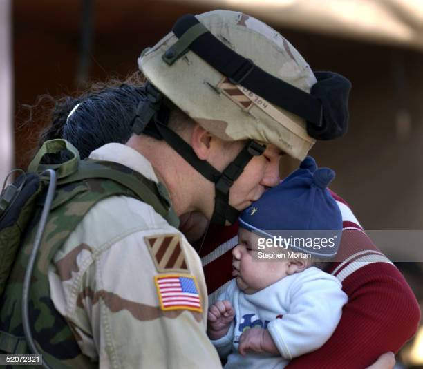 Army Spc. Jerald Duncan kisses his son, Bryce, goodbye during the deployment of the 3rd Infantry Division January 27, 2005 at Fort Stewart, Georgia....