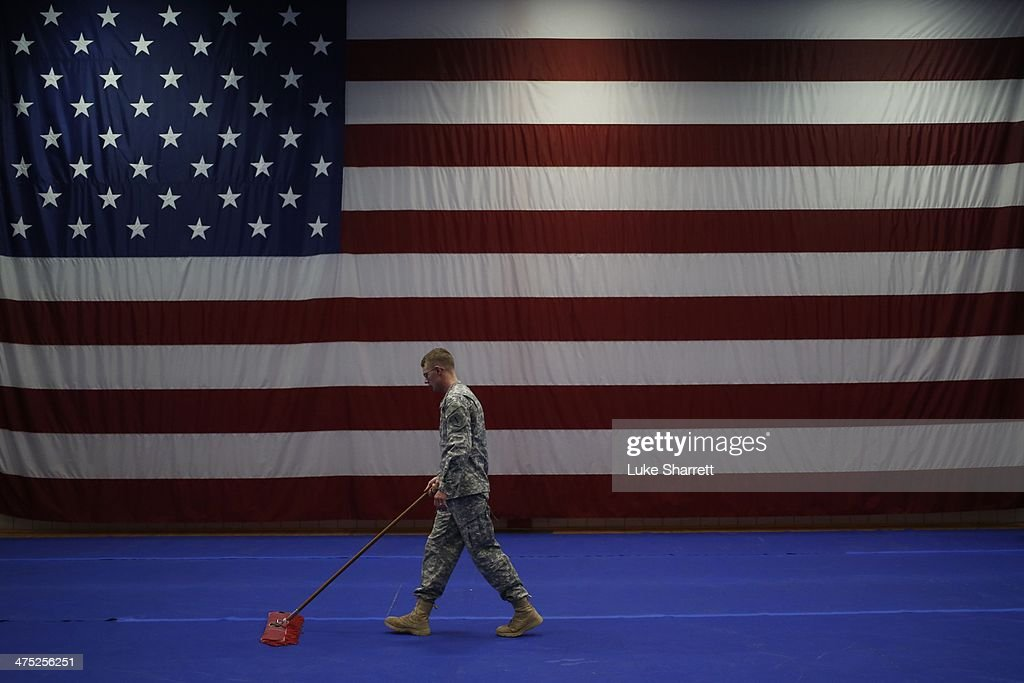 Army Spc. Nathan Bookout sweeps the floor following a welcome home ceremony for members of the U.S. Army's 3rd Brigade Combat Team, 1st Infantry Division in the Natcher Physical Fitness Center on Fort Knox on February 27, 2014 in Fort Knox, Kentucky. About 100 soldiers returned to Fort Knox after a nine-month combat deployment conducting village stability operations and working alongside Afghan military and police forces.