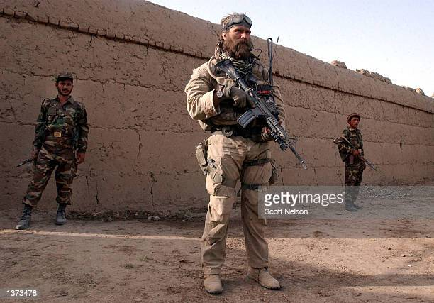 S Army Special Forces soldier nicknamed Cowboy stands guard with Afghan Military Force soldiers during an operation August 24 2002 in the village of...