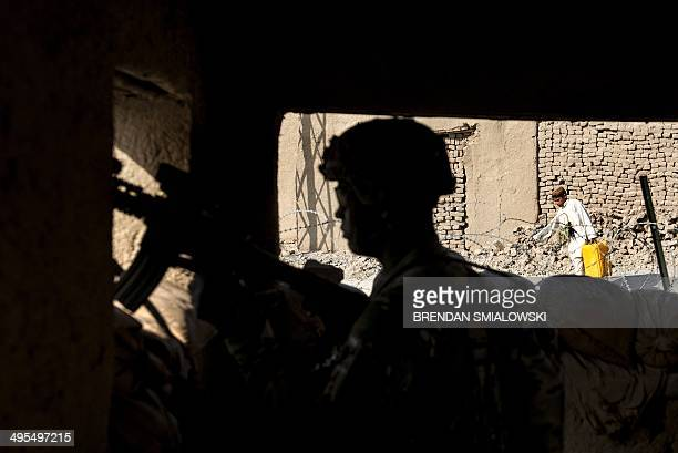 US Army Specialist Antonio Henderson of Texas stands guard at a police station while US solider meet with Afghan police near Kandahar Airfield on...