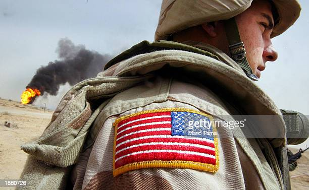 S Army Specialist Chad Morton of George West Texas stands next to a burning oil well at the Rumayla oil fields March 27 2003 in Rumayla Iraq Several...