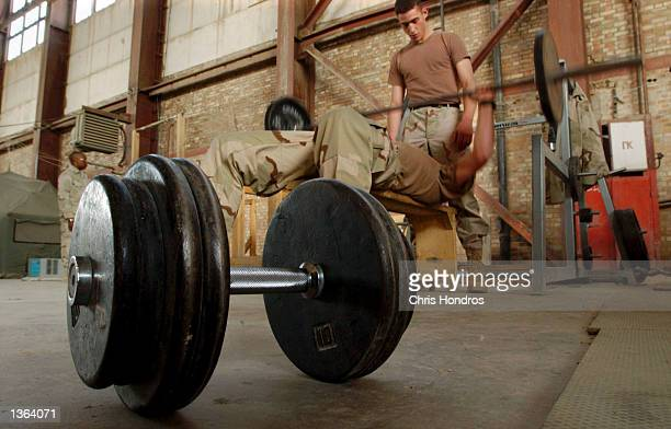 S Army Specialist Jason Allenbaugh of Pittsburgh Pennsylvania spots Staff Sgt Max Barnum of St George Utah lifing weights in a hanger September 2...