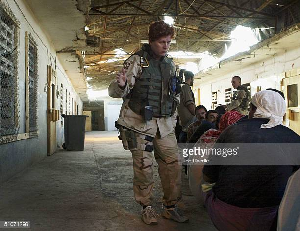 S Army Specialist Lucky Berger from Portage Michigan of the 391st Military Police Battalion keeps an eye on prisoners as they wait to be processed...