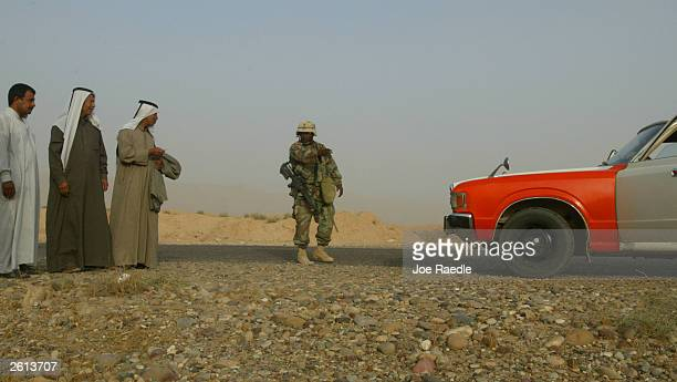 Army Specialist Rhylin Price from New Madrid, Misouri of the 299th Engineering Battalion,4th Infantry Division gestures to Iraqi men to return to...