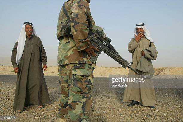 Army Specialist Rhylin Price from New Madrid, Misouri of the 299th Engineering Battalion, 4th Infantry Division stands between Iraqi men while...