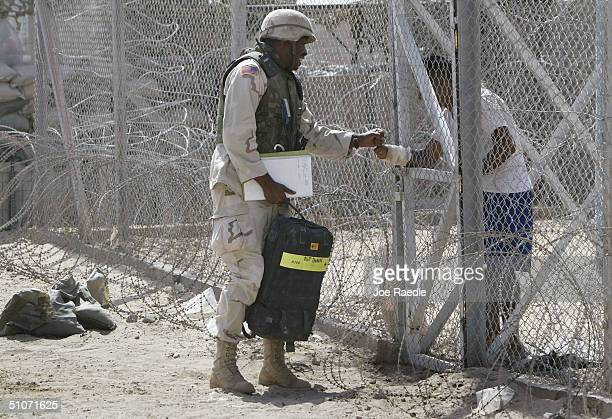 S Army Specialist Richard Williams from Erie Pennsylvania of the 391st Military Police battalion interacts with a prisoner who is housed at Abu...