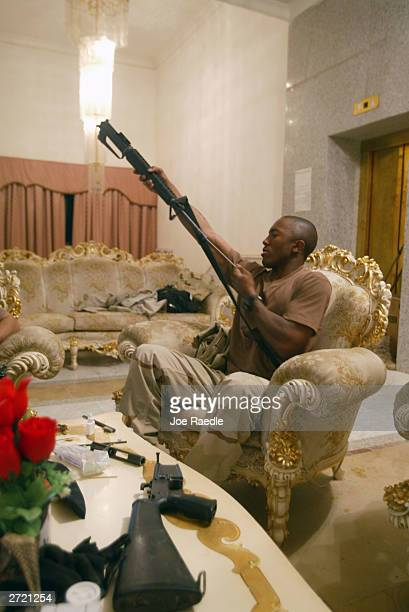 S Army Specialist Ronald Johnson from Cleveland Ohio of the 4th Infantry Division cleans his weapon in a former palace of Saddam Hussein November 12...