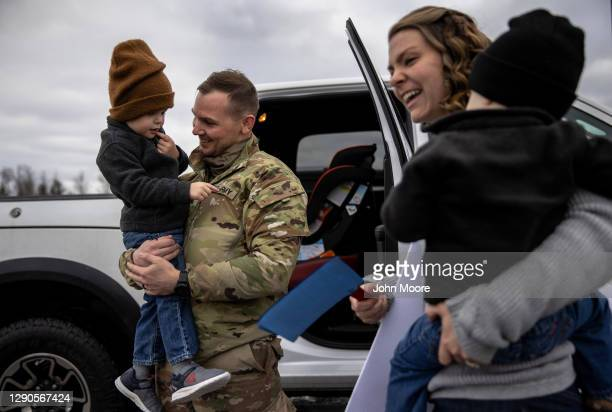 Army SSG. Matthew Peters holds his son Eli while reuniting with his family after returning home from a 9-month deployment to Afghanistan on December...