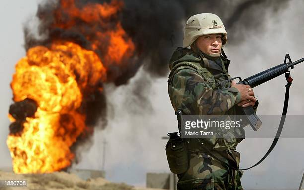 S Army Staff Sergeant Robert Dominguez of Mathis Texas stands guard next to a burning oil well at the Rumayla oil fields March 27 2003 in Rumayla...