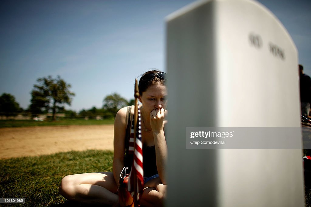 U.S. Army Staff Sgt. Lindsay Natiw of Plymouth, Michigan, sits next to U.S. Army Corporal Jacob Turbett's headstone on Memorial Day in Section 60 of Arlington National Cemetery May 31, 2010 in Arlington, Virginia. Natiw attended the same high school as Turbett and she took a photograph of his grave site to send to Turbett's mother because she could not be there for the holiday. This is the 142nd Memorial Day observance at the cemetery.
