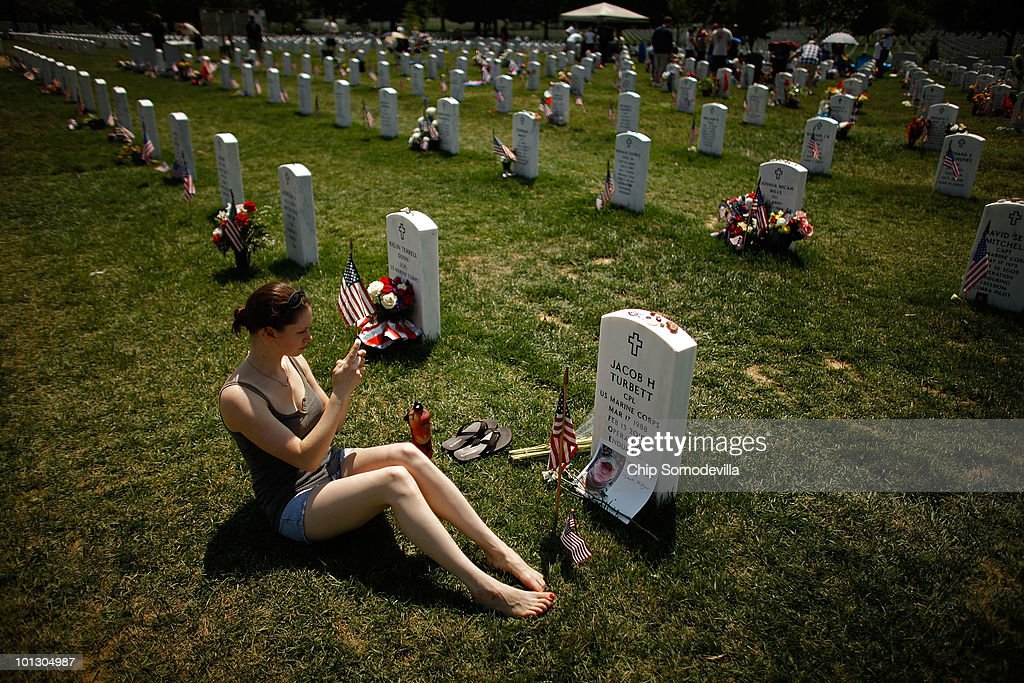 U.S. Army Staff Sgt. Lindsay Natiw of Plymouth, Michigan, takes a photograph of U.S. Army Corporal Jacob Turbett's headstone on Memorial Day in Section 60 of Arlington National Cemetery May 31, 2010 in Arlington, Virginia. Natiw attended the same high school as Turbett and she took a photograph of his grave site to send to Turbett's mother because she could not be there for the holiday. This is the 142nd Memorial Day observance at the cemetery.