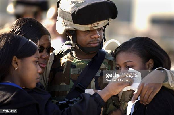 Army Staff Sgt. Scotty Walker hugs his wife Adella and his twin daughters, Sheri and Teri goodbye during the deployment of the 3rd Infantry Division...