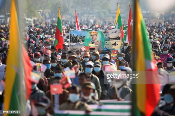 Army supporters carry a banner showing a portrait of military chief General Min Aung Hlaing during a rally Naypyidaw on February 4, 2021 following a...