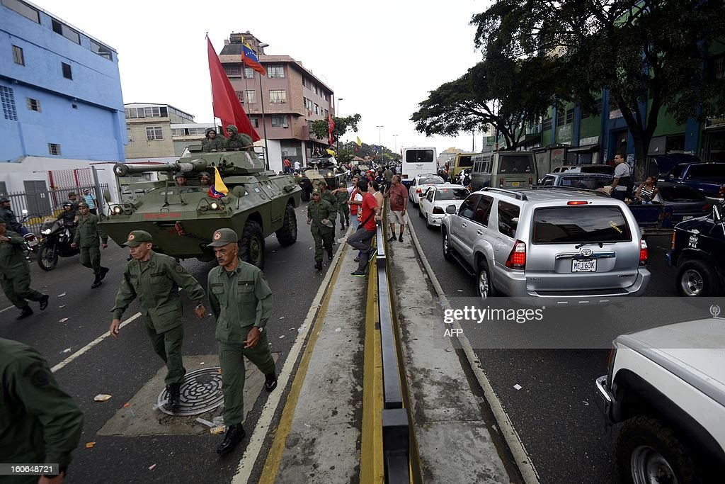 Army tanks and supporters of Venezuelan President Hugo Chavez take to the streets to conmemorate the 1992 failed coup led by Chavez, who was an army lieutenant colonel, against then president Carlos Andres Perez, in Caracas, on February 4, 2013. Ailing President Hugo Chavez, who had cancer surgery in December, is doing much better and recovering, Cuban leader Fidel Castro said in remarks published Monday. AFP PHOTO/Leo RAMIREZ