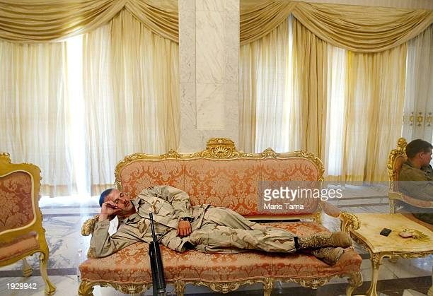 S Army Third Infantry Division Sgt Roscoe Archer of Fort Stewart Georgia catches a nap on a couch in the Republican Presidential Palace April 14 2003...