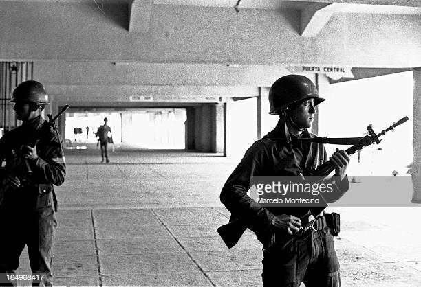 CONTENT] Army troops guards the National Stadium where more than 7000 people were being held by the new military government Sept 1973