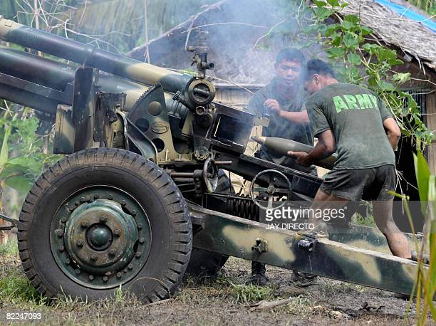 Army troops load ammunition into a 105 mm Howitzer canon and fire into Moro Islamic Liberation Front positions in Aleosan North Cotabato Province...