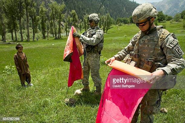 US Army troops of the 82nd Airborne Division rollup a dropzone marker used for an humanitarian airdrop | Location Near Mondi Village Nuristan...