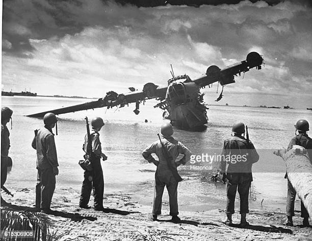 US Army troops pause for a look at a Japanese seaplane during the battle of Makin The plane was under repair in the lagoon when the invasion started...