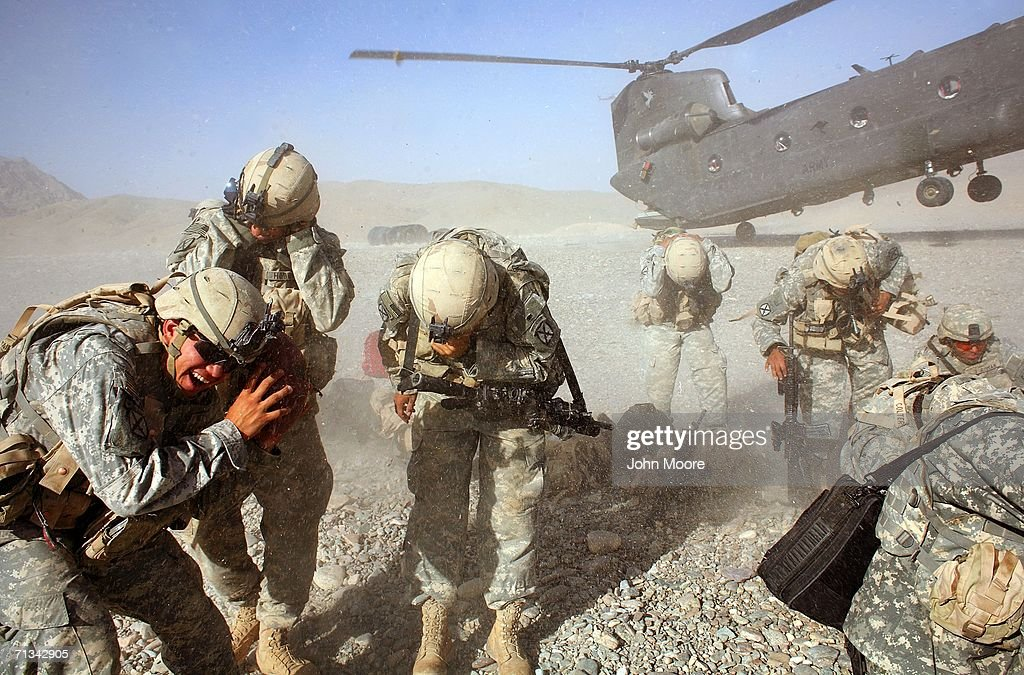 U.S. Army troops shield themselves from the dust of an Australian Chinook helicopter arriving to transport them from their base at Deh Afghan on June 30, 2006 in the Zabul province of southern Afghanistan. Coalition forces are moving around the Afghan south while on Operation Mountain Thrust in search of Taliban insurgents.