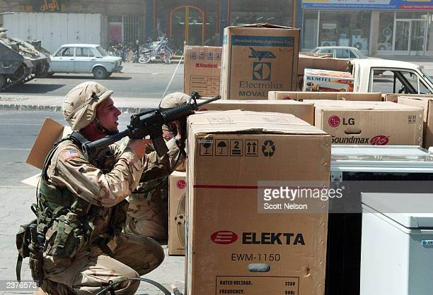 S Army troops take cover behind appliances outside an Iraqi market during a gun battle with unknown gunmen that followed a rocket propelled grenade...
