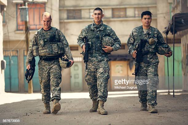 army troops walk down a street in combat. - army soldier stock pictures, royalty-free photos & images
