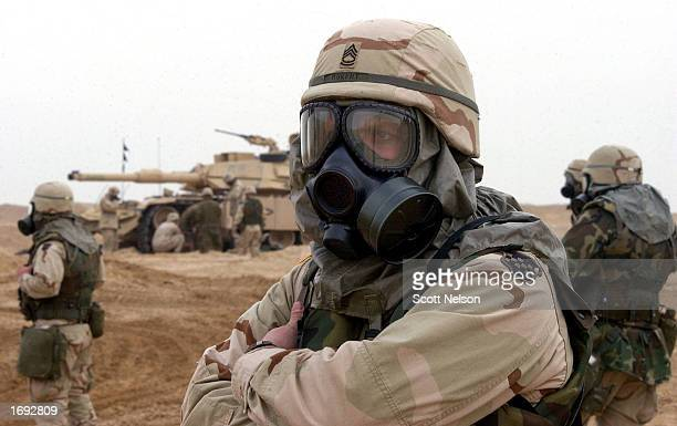 S Army troops wear protective chemical and biological gear during task force manuevers December 18 2002 near the Iraqi border in the Kuwaiti The US...