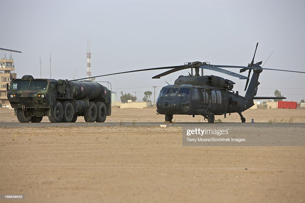 A U.S. Army UH-60 Black Hawk helicopter with its refueler truck at COB Speicher, Tikrit, Iraq. : Stock Photo