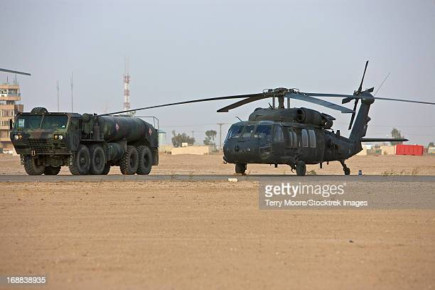 A U.S. Army UH-60 Black Hawk helicopter with its refueler truck at COB Speicher, Tikrit, Iraq.