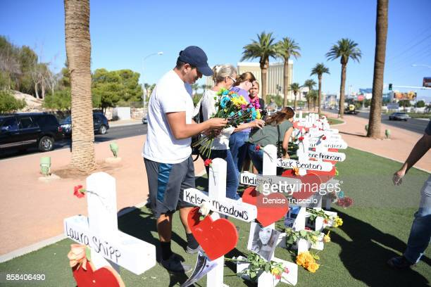 S Army veteran Adam Arizaga of Nevada places flowers on a cross at the Welcome to Fabulous Las Vegas sign on October 6 2017 in Las Vegas Nevada...