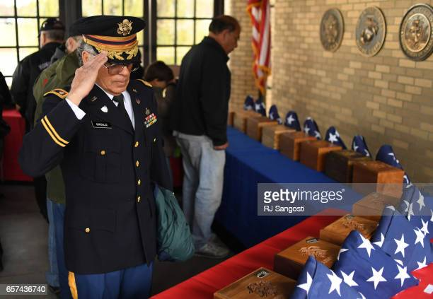 Army Veteran Alvaro Gonzalez salutes each urn after the final interment of the unclaimed remains of twenty two Veterans at Fort Logan National...