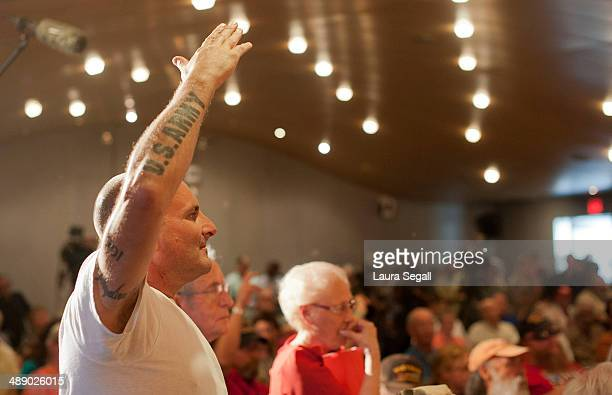 Army Veteran Mark Howeya patient at the Phoenix VA raises his hand to ask a question at a forum at the Burton Barr Central Library on May 9 2014 in...