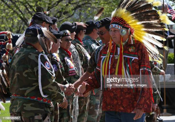 Army veteran Peter Thompson of the White Earth reservation shook the hands of fellow tribal honor guard members at the start of the plaque ceremony...
