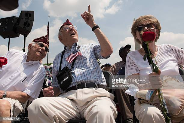 Army Veterans Harold Radish left Eli Linden center and his wife right watch the array of World War II aircraft fly over the National Mall celebrating...