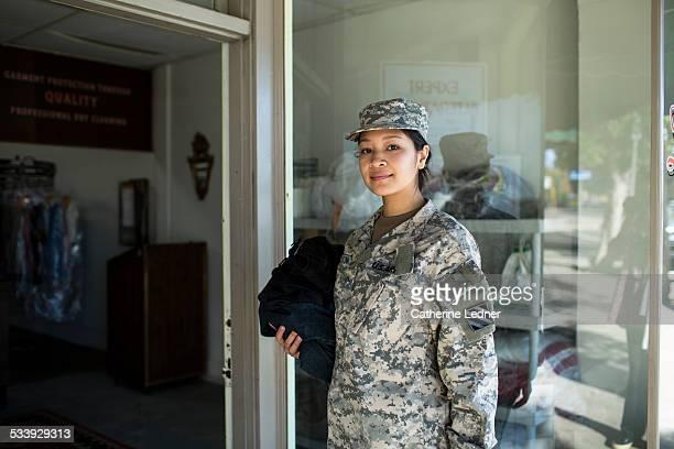 army woman bringing laudry to dry cleaners - objetivo militar imagens e fotografias de stock
