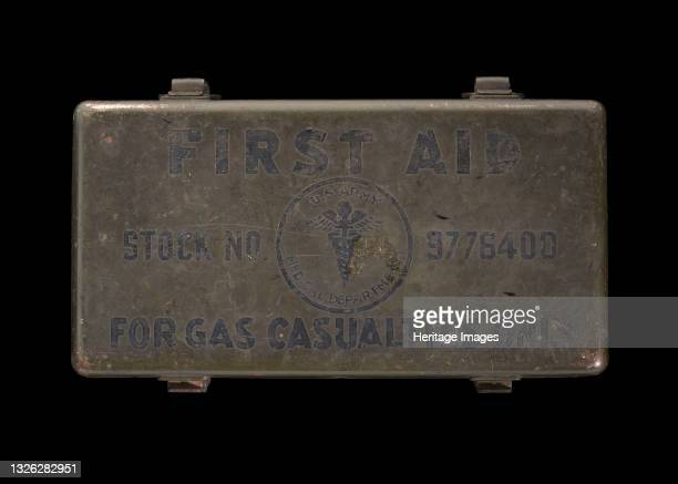 Army-issued first aid kit from World War II labeled [For Gas Casualties Only]. The green painted metal box has four latches on each side so, that...