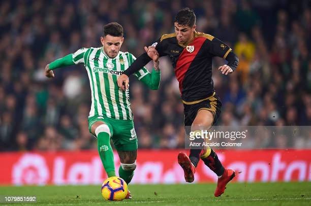 Arnaldo Antonio Sanabria of Real Betis Balompie competes for the ball with Santiago Comesana of Rayo Vallecano during the La Liga match between Real...