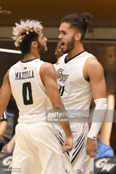 Arnaldo Toro and Justin Mazzulla of the George Washington Colonials celebrate a basket during a college basketball game against the Stony Brook...